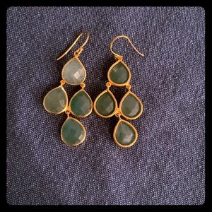 Gold statement earrings with green stones.